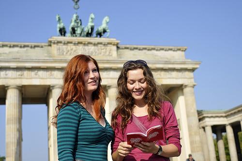 Schülerinnen stehen lächelnd vor dem Brandenburger Tor in Berlin