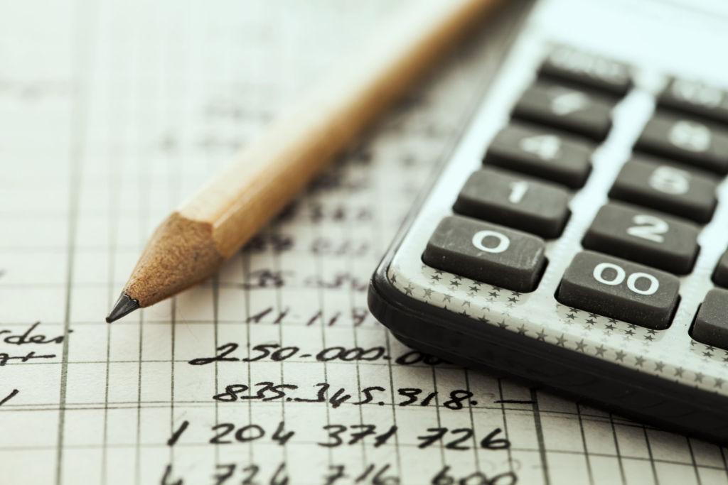 Taschenrechner und Bleistift sind auf einer Kostenafufstellung platziert.