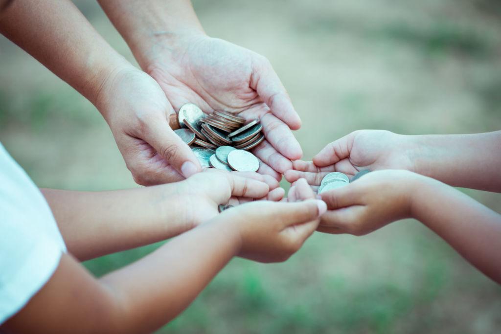 Sechs Hände halten viele Münzen in ihren Händen.