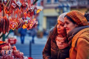 Zwei junge Frauen stehen an einer Weihnachtsmarktbude und suchen sich süßes weihnachtliches Gebäck aus.