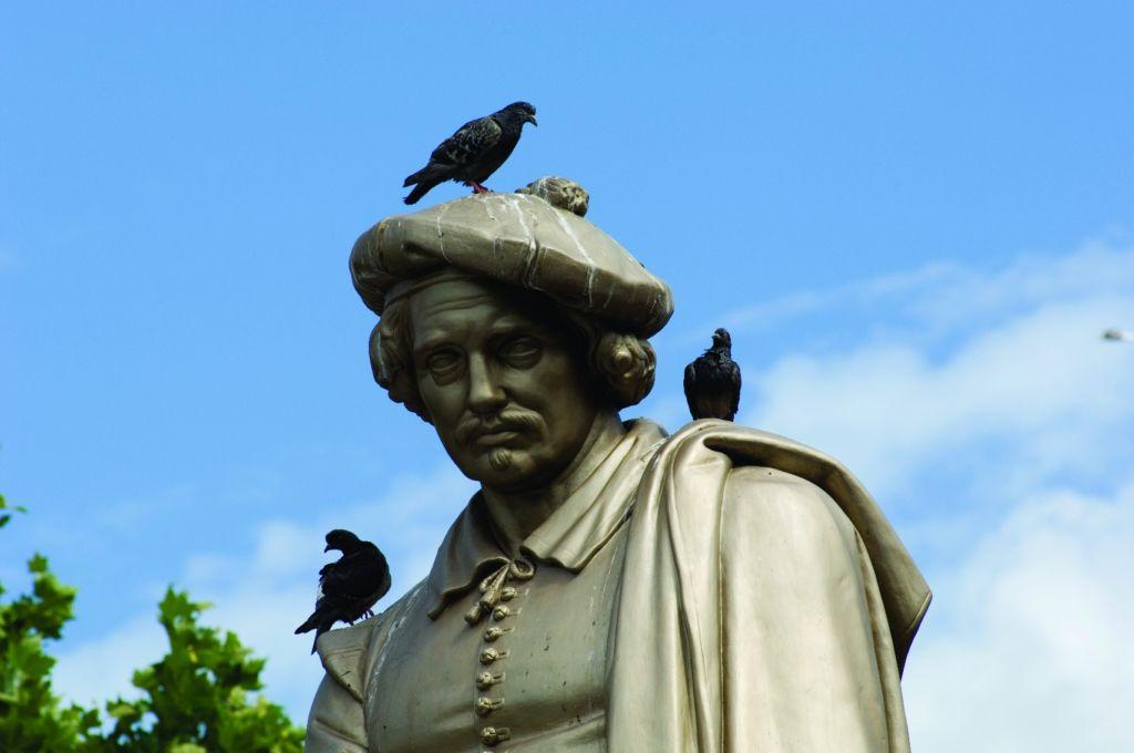 Rembrandt Statue mit Vögeln und blauem Himmel