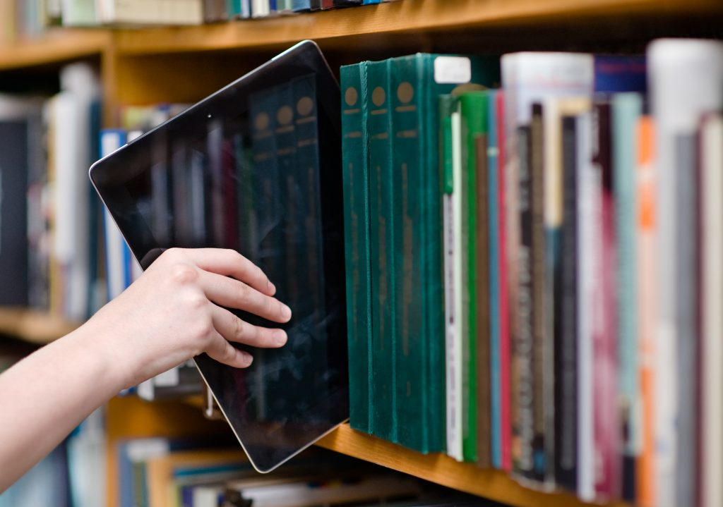 Schüler stellt ein Tablet, als digitales Medium, in ein Bücherregal