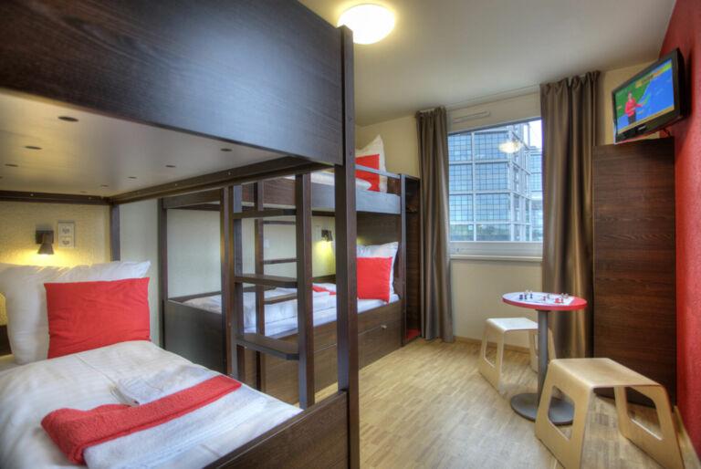 Blick in ein Zimmer mit Betten und Sitzgelegenheit im MEININGER Hauptbahnhof Berlin